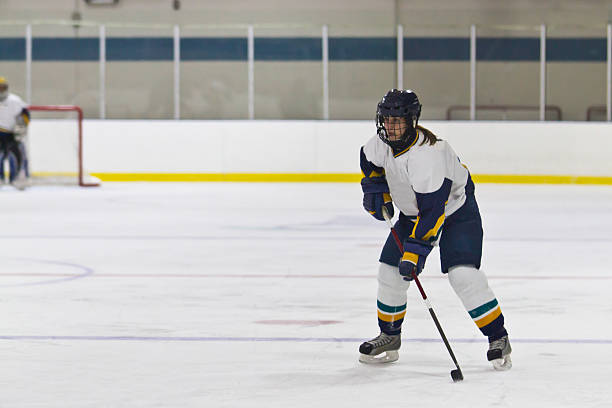 Female ice hockey player skating during the game stock photo