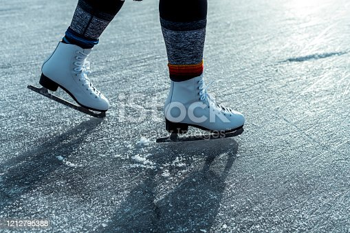 A female legs with ice skates on ice surface.