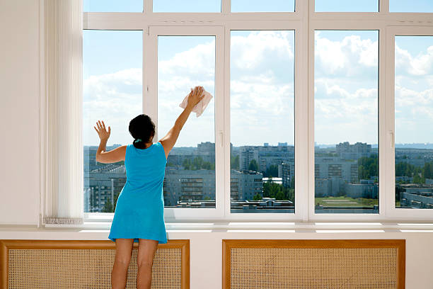 A female in a blue dress cleaning tall windows stock photo