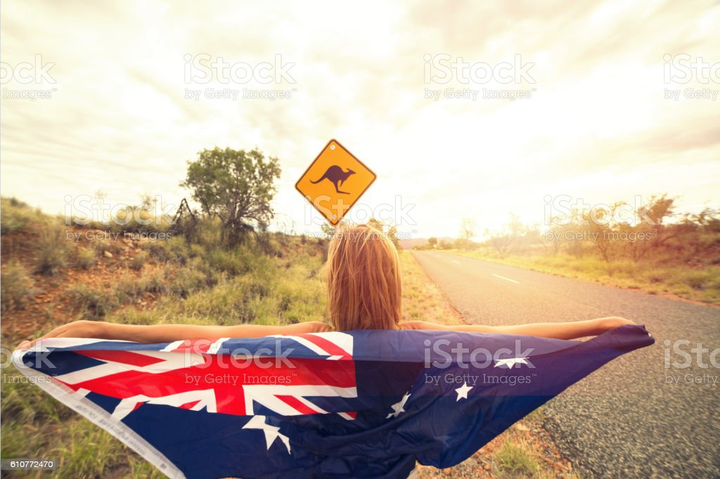 Female in Australia holding flag near kangaroo sign stock photo