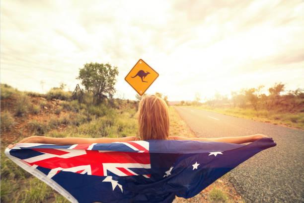 Female in Australia holding flag near kangaroo sign stock photo