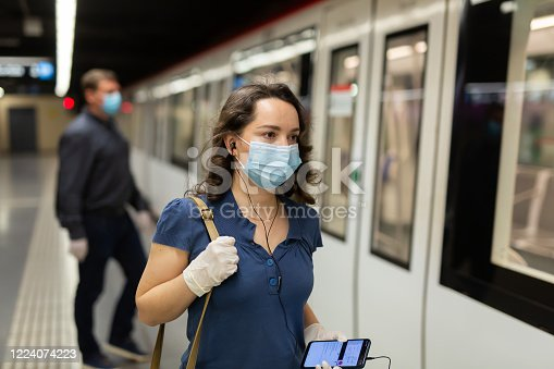 istock Female in face mask and earphones on subway platform 1224074223
