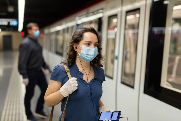Female in face mask and earphones on subway platform stock photo