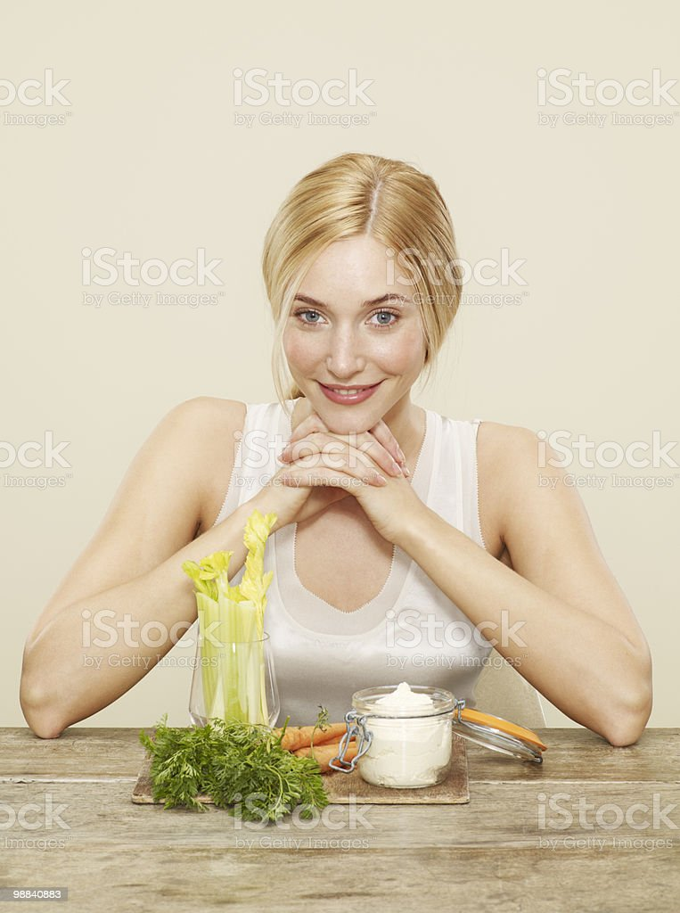 female in front of celery, carrots and humous Lizenzfreies stock-foto