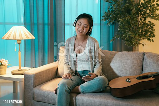 Beautiful asian japanese girl in headphones listening to music holding smart phone and smiling while sitting on couch at home in dark night. female stay up late in midnight enjoy melody on headset