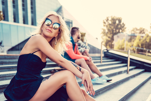 Female in sunglasses sitting on stairs.