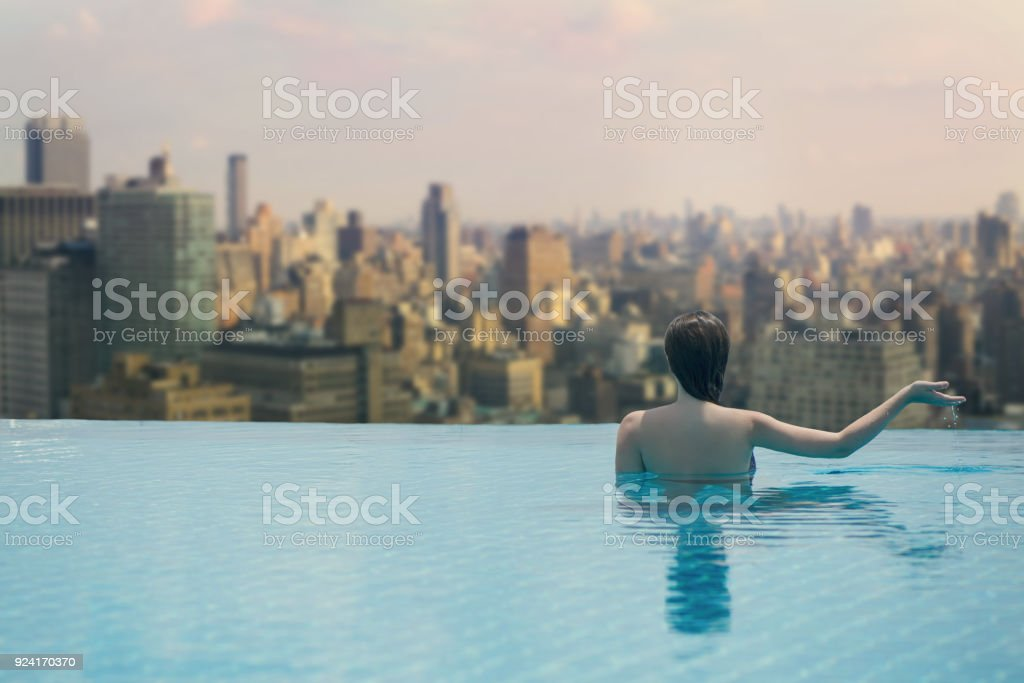 Female In The Pool On The Roof On The Background Of Skyscrapers Of
