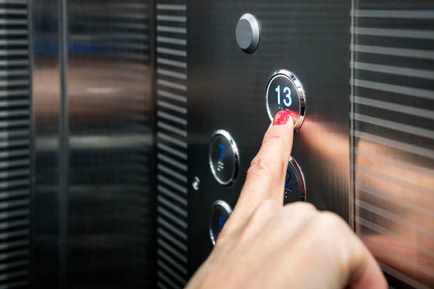 Female in the suit pushing the button it the elevator. Close-up photo of a smart girl, who is an office worker, pushing the lift's button. stock photo