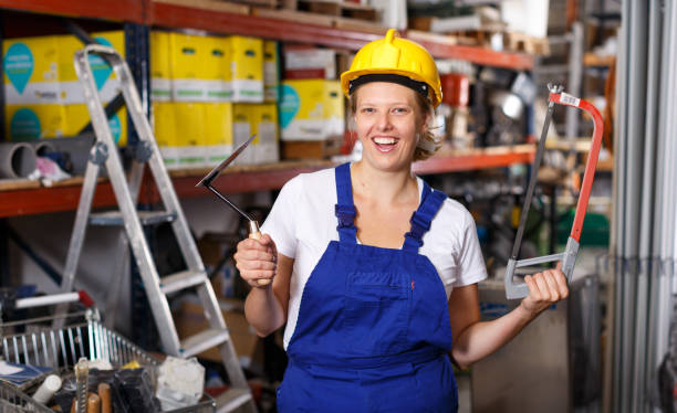 Female  in uniform and helmet holding saw and standing near racks in build store stock photo