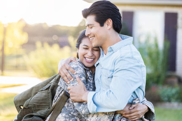 Female in uniform shares a hug with her husband Young, Hispanic female in uniform hugs her husband tightly, after she has just arrived home from duty. She still holds her bag on her shoulder, while they stand outside their home. husband stock pictures, royalty-free photos & images