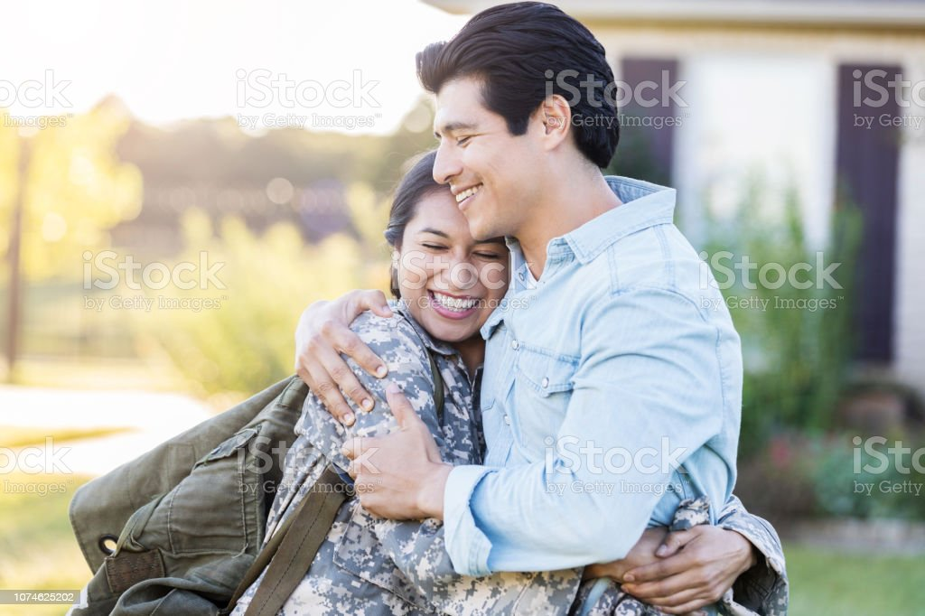Female in uniform shares a hug with her husband stock photo