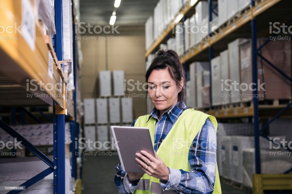 Woman holding digital tablet and putting in data in a big warehouse.