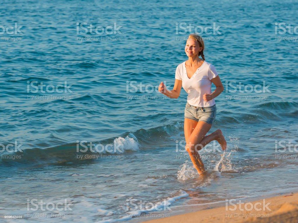 Mujer en blanco t-shirt es correr - Foto de stock de Adulto libre de derechos