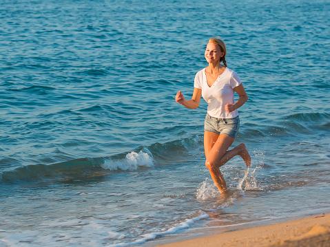 Mujer En Blanco Tshirt Es Correr Foto de stock y más banco de imágenes de Adulto
