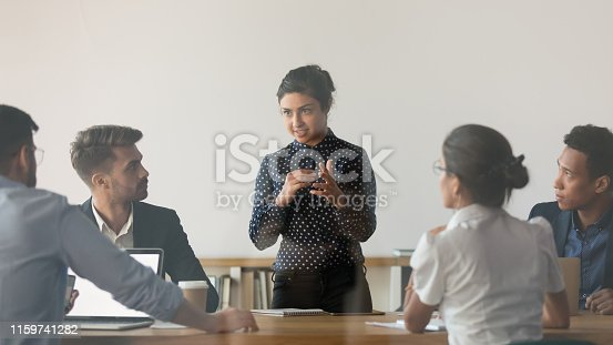 Indian female coach stand holding meeting with diverse work team discussing sharing ideas in conference room, multiethnic people or colleague brainstorm talking cooperating at office briefing
