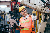 istock Female industrial engineer or technician worker in hard helmet and uniform using laptop checking on robotic arm machine. woman work hard in heavy technology invention industry manufacturing factory 1219401451