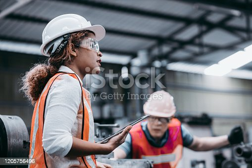 istock Female industrial engineer wearing a white helmet while standing in a heavy industrial factory behind she talking with workers, Various metal parts of the project 1205756496
