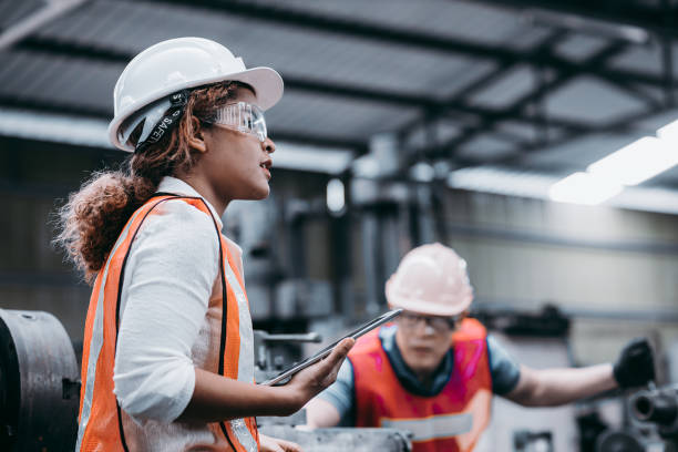 Female industrial engineer wearing a white helmet while standing in a heavy industrial factory behind she talking with workers, Various metal parts of the project Female industrial engineer wearing a white helmet while standing in a heavy industrial factory behind she talking with workers, Various metal parts of the project manufacturing stock pictures, royalty-free photos & images