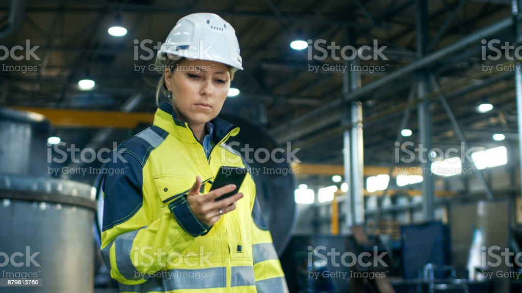 Female Industrial Worker in the Hard Hat Uses Mobile Phone While Walking Through Heavy Industry Manufacturing Factory. In the Background Various Metalwork Project Parts Lying Female Industrial Worker in the Hard Hat Uses Mobile Phone While Walking Through Heavy Industry Manufacturing Factory. In the Background Various Metalwork Project Parts Lying Adult Stock Photo