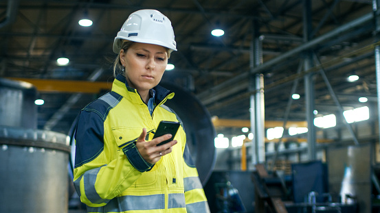 Female Industrial Worker In The Hard Hat Uses Mobile Phone While Walking Through Heavy Industry Manufacturing Factory In The Background Various Metalwork Project Parts Lying Stock Photo - Download Image Now
