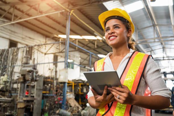 pracownica przemysłowa pracująca i sprawdzająca maszynę w dużej fabryce przemysłowej z wieloma urządzeniami. - kask ochronny odzież ochronna zdjęcia i obrazy z banku zdjęć