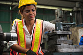 Female industrial worker working and checking machine in a large industrial factory with many equipment.