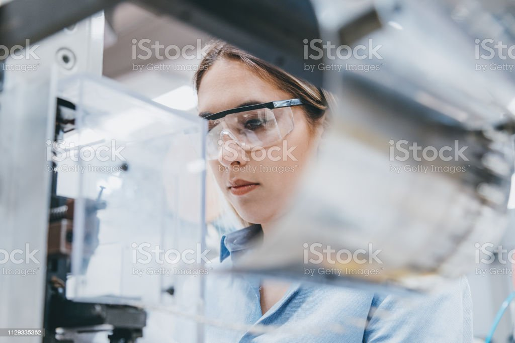 Female industrial worker working with manufacturing equipment in a factory Professional young industrial factory woman employee working with machine parts putting, checking and testing industrial equipments cables in large Electric electronics wire and cable manufacturing plant factory warehouse Laboratory Stock Photo