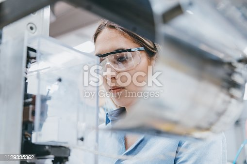 Professional young industrial factory woman employee working with machine parts putting, checking and testing industrial equipments cables in large Electric electronics wire and cable manufacturing plant factory warehouse