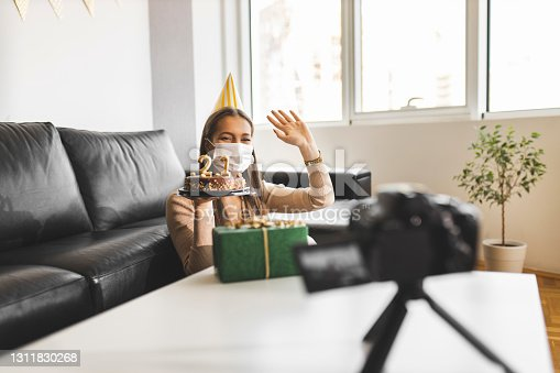 Female influencer celebrating her 21st birthday at home, making a wish and filming vlog