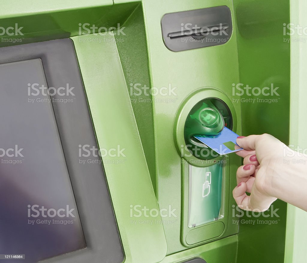 Female inserts a plastic card in the ATM stock photo