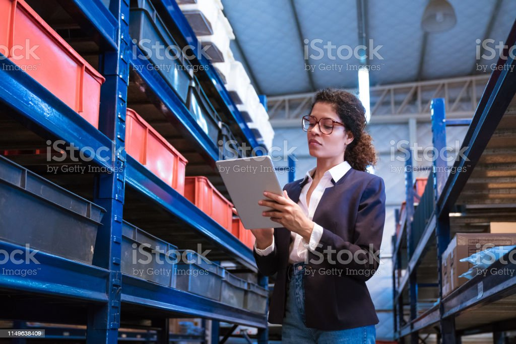 Female inspector using digital tablet by racks Female manager using digital tablet by racks. Inspector is on visit in manufacturing industry. She is standing at distribution warehouse. 30-34 Years Stock Photo