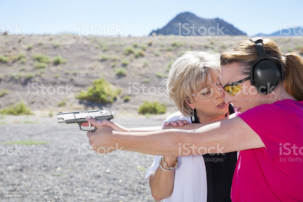Female instructor explaining gun safety at an outdoor range royalty-free stock photo