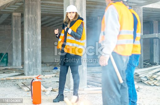 Female Instructor explaining how to use fire extinguisher on construction site