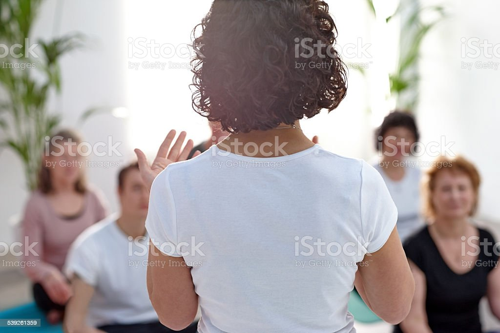 Female instructor guiding student during yoga class stock photo