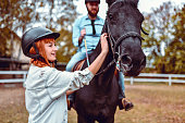 Female Instructor Leading Handsome Male On Horse