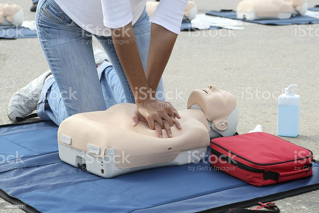 Female instructor showing CPR on training doll stock photo