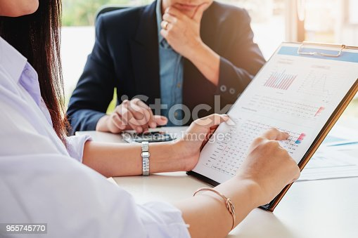 950986656istockphoto female interview pointing financial document with business man interviewer using calculator. 955745770