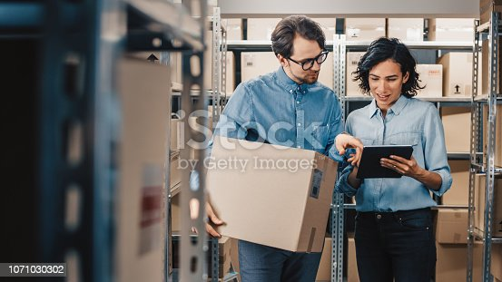 istock Female Inventory Manager Shows Digital Tablet Information to a Worker Holding Cardboard Box, They Talk and Do Work. In the Background Stock of Parcels with Products Ready for Shipment. 1071030302