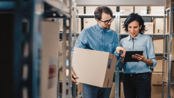 weiblich-inventar-manager zeigt digital tablet informationen einer arbeitskraft karton halten, sie sprechen und arbeiten. im hintergrund bestand der parzellen mit produkte bereit für den versand. - konsum stock-fotos und bilder