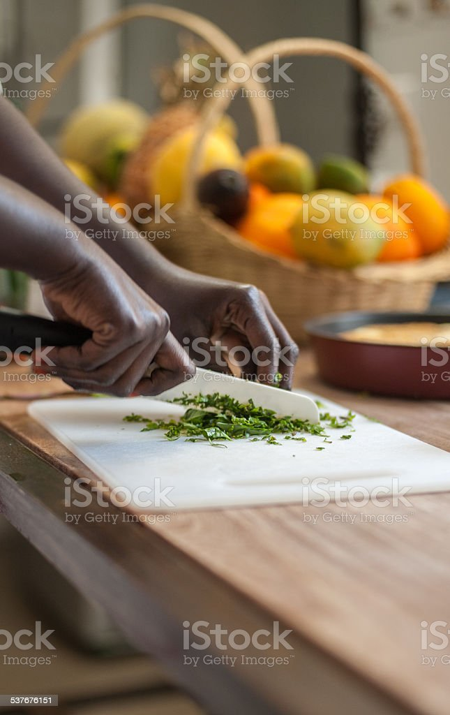 Female is chopping herbs on a white board stock photo
