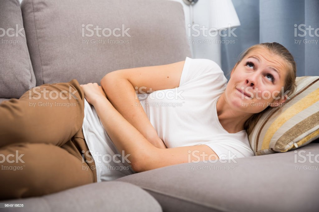 Female is having stomach ache and she lying on sofa royalty-free stock photo