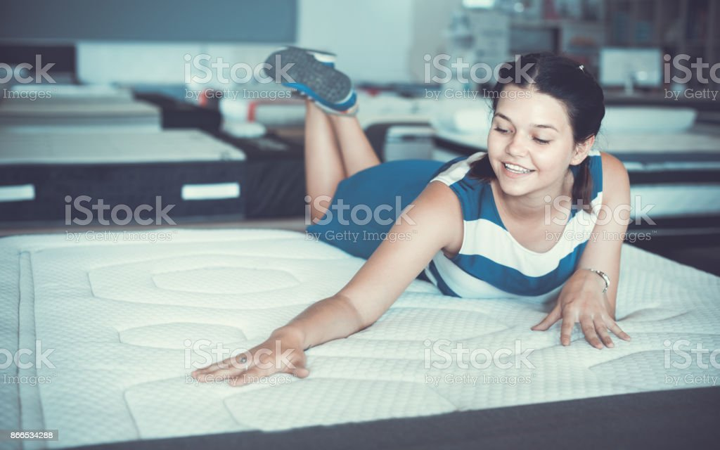Happy smiling female is lying on mattress for testing it in the store.