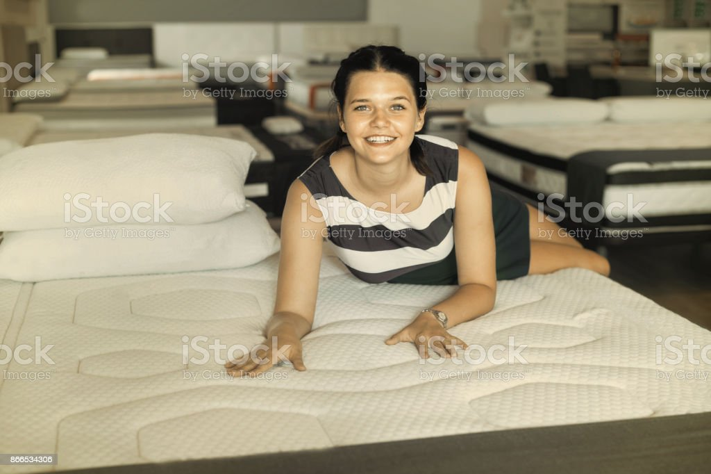 Happy cheerful positive smiling female is lying on mattress for...