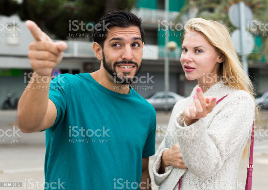 Female is showing to latino tourist the way to hotel stock photo