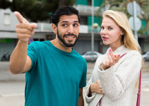 Female is showing to latino tourist the way to hotel Female is showing to latino tourist the way to hotel in city. stranger stock pictures, royalty-free photos & images