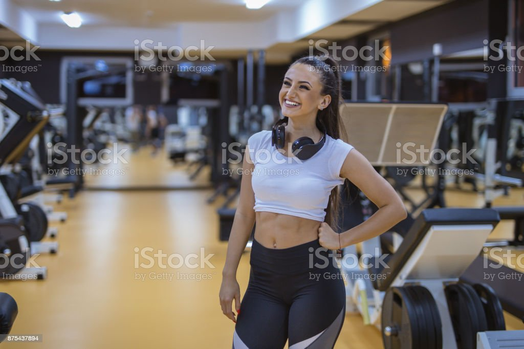 Female is smiling at gym , she is posing and looking very happy stock photo