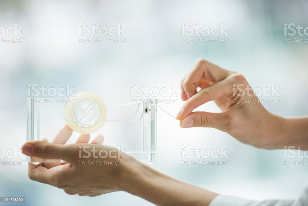 Female is using adhesive tape royalty-free stock photo