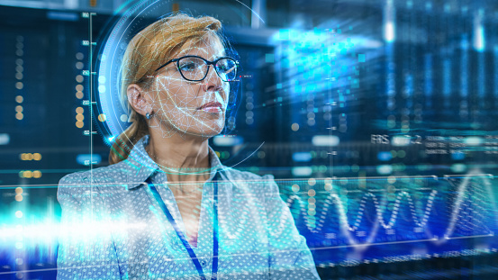 istock Female IT Engineer Identified by Biometric Facial Recognition Scanning Process in Data Center Server Room. Futuristic Concept: Projector Identifies Individual by Illuminating Face by Lines. 1159763173