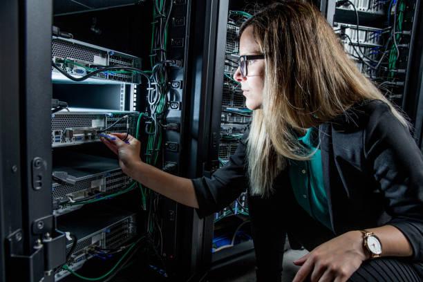 vrouwelijke ingenieur werken in serverruimte - datacenter stockfoto's en -beelden