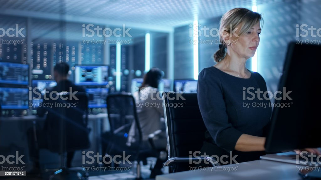 Female IT Engineer Works on Her Desktop Computer in Government Surveillance Agency. In the Background People at Their Workstations with Multiple Screens Showing Graphics. Female IT Engineer Works on Her Desktop Computer in Government Surveillance Agency. In the Background People at Their Workstations with Multiple Screens Showing Graphics. Adult Stock Photo